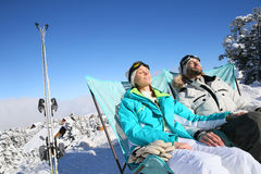 Couple of skiers relaxing and taking sun on the slopes Royalty Free Stock Photo