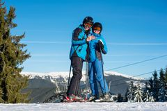 Couple skiers standing on mountain top at sunny winter day Stock Image