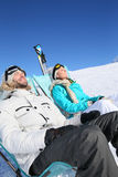 Couple of skiers sunbathing Royalty Free Stock Photography