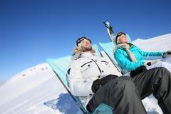 Couple of skiers taking a break sunbathing Royalty Free Stock Images