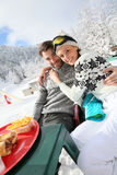 Couple of skiers taking a lunch brealk on the slopes Royalty Free Stock Photos