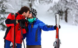 Couple on a skiing holiday kissing. Couple kissing each-other at a winter forest before go out skiing Stock Photography