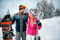 Couple skiing and snowboarding enjoying in snowy mountains toget. Young couple skiing and snowboarding enjoying in snowy mountains together Royalty Free Stock Photos
