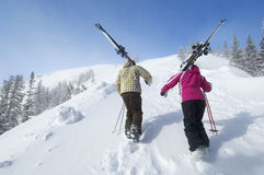 Couple With Skis Hiking Up Slope Stock Photos