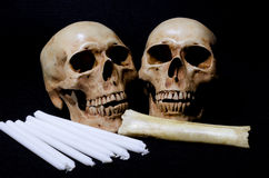 A couple of skull with candles and bone on black background Royalty Free Stock Photo