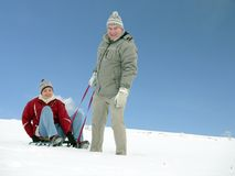 Couple with sled. Young man tugging his wife sitting on sledge on snow over blue sky Royalty Free Stock Images
