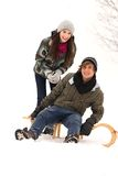 Couple on sled. Young couple on sled in snow Stock Images