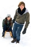 Couple on sled. Man pulling woman on sled Stock Photo