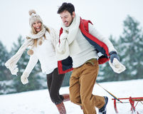 Couple with sled running through Royalty Free Stock Images