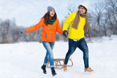 Couple with sled in snow Royalty Free Stock Photos
