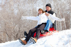 Couple sledding Stock Photos