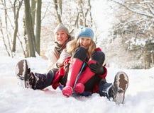 Couple Sledging Through Snowy Woodland Royalty Free Stock Photos