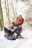 Couple Sledging Through Snowy Woodland Royalty Free Stock Images