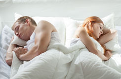 Couple sleeping back to back Stock Photos