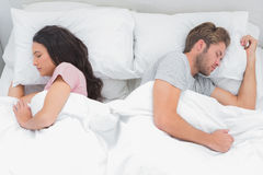 Couple sleeping back to back in their bed Royalty Free Stock Image