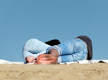 Couple sleeping on the beach. With blue sky as a background Royalty Free Stock Images