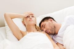 Couple sleeping in bed at home. People, family, bedtime and insomnia concept - unhappy women having sleepless night with sleeping and snoring men in bed at home Stock Photography