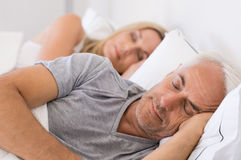 Couple sleeping in bed. Senior men and women sleeping. Senior men and women resting with eyes closed. Mature couple sleeping together in their bed Royalty Free Stock Photos