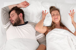 Couple sleeping in bed.  Woman can`t sleep because of her man`s snoring Stock Images