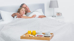 Couple sleeping with breakfast tray on bed Royalty Free Stock Photography