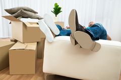 Couple sleeping on couch in new house. Couple Sleeping On Couch In New Home With Cardboard Boxes Around Royalty Free Stock Images