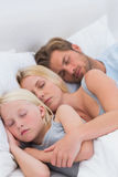 Couple sleeping with daughter Stock Images