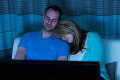 Couple sleeping in front of television Royalty Free Stock Photos