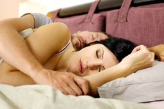 Couple sleeping peacefully in bed during vacation in hotel Stock Photography