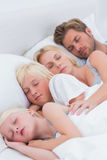 Couple sleeping with their children Stock Photo