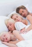 Couple sleeping with their children Stock Photo