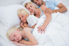 Couple sleeping with their cute children Stock Photography