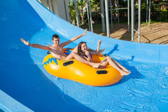 Couple sliding down a water slide Royalty Free Stock Photography