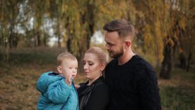 A couple with a small boy in autumn Park. stock footage