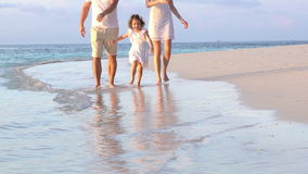 A couple with a small child walking a beach. Slow motion. stock footage