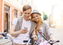 Couple with smartphone and bicycles in the city Stock Image