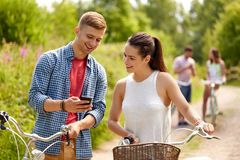 Couple with smartphone and bicycles in summer royalty free stock images