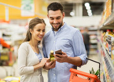 Couple with smartphone buying olive oil at grocery. Shopping, food, sale, consumerism and people concept - happy couple with smartphone buying olive oil at Royalty Free Stock Photos