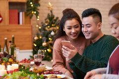 Couple with smartphone at dinner table royalty free stock images