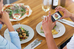 Couple with smartphone photographing food at cafe Royalty Free Stock Image