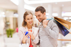 Couple with smartphone and shopping bags in mall. Sale, consumerism, technology and people concept - happy young couple with shopping bags and smartphone talking Royalty Free Stock Images