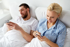 Couple with smartphones in bed at home Stock Photo