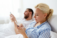 Couple with smartphones in bed at home Stock Images