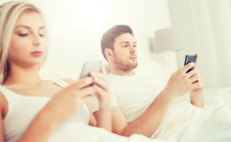 Couple with smartphones in bed Stock Image