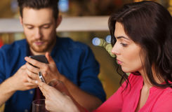 Couple with smartphones dining at restaurant Stock Photography
