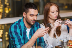 Couple with smartphones dining at restaurant Stock Photos