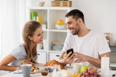 Couple with smartphones having breakfast at home Stock Photography