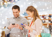 Couple with smartphones and shopping bags in mall. Sale, consumerism, technology and people concept - happy couple with shopping bags and smartphones texting Royalty Free Stock Photos