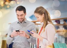 Couple with smartphones and shopping bags in mall. Sale, consumerism, technology and people concept - happy young couple with shopping bags and smartphones in royalty free stock photos