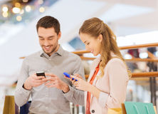 Couple with smartphones and shopping bags in mall. Sale, consumerism, technology and people concept - happy young couple with shopping bags and smartphones in stock photos