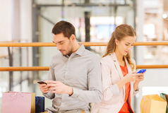 Couple with smartphones and shopping bags in mall Royalty Free Stock Photography